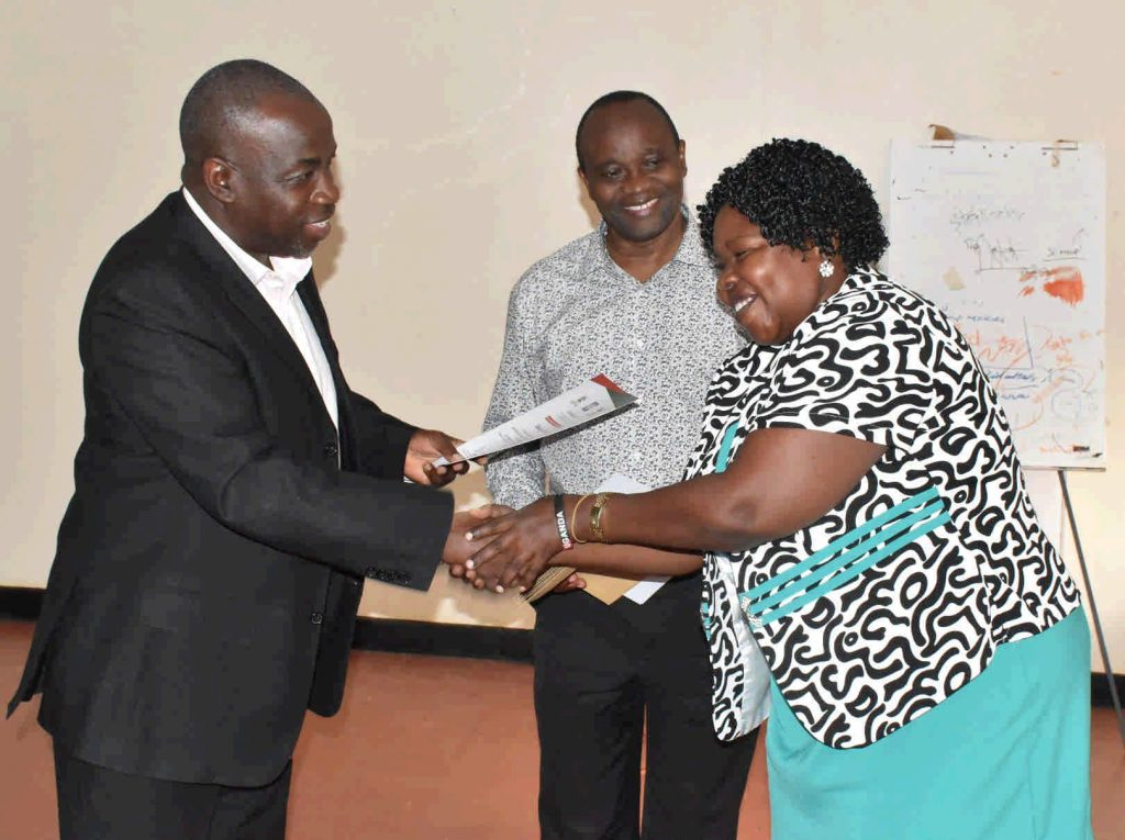 - Commissioner Dr. Patience Rwamigisha and Prof. Kaaya handover the certificate of attendance to one of the participants
