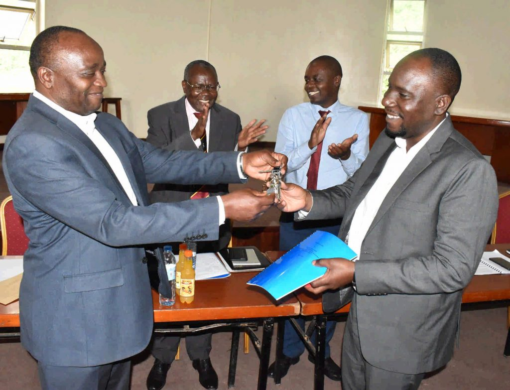 - Dr. Ivan Muzira Mukisa (R) receives the keys to the office from from Prof. Kaaya