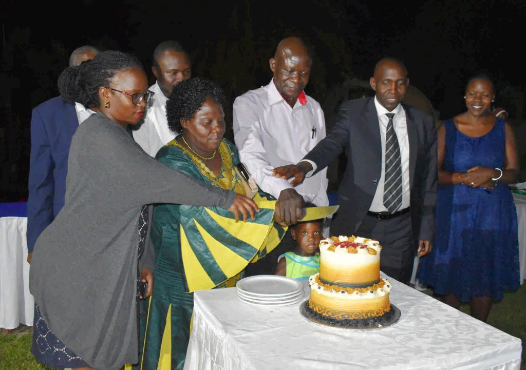 - Dr. JS Tenywa flanked by his family, Principal and Head of department cut the cake
