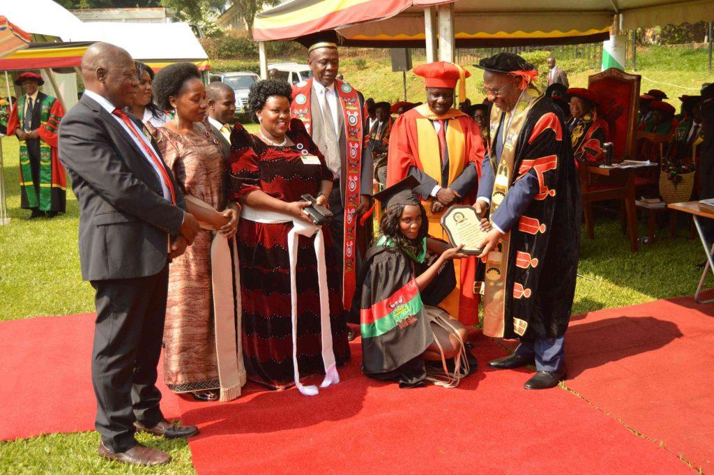 - Ms. Namayengo Sarah receiving a plaque from the Dr. Ruhakana Rugunda