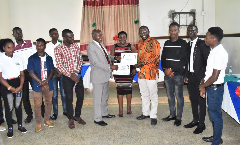 - Dr. Owinyi David in a suit presents a certificate of appreciation from the students to the Recess term coordinators Dr. Sarah Akello and Mr. Anthony Mwijje