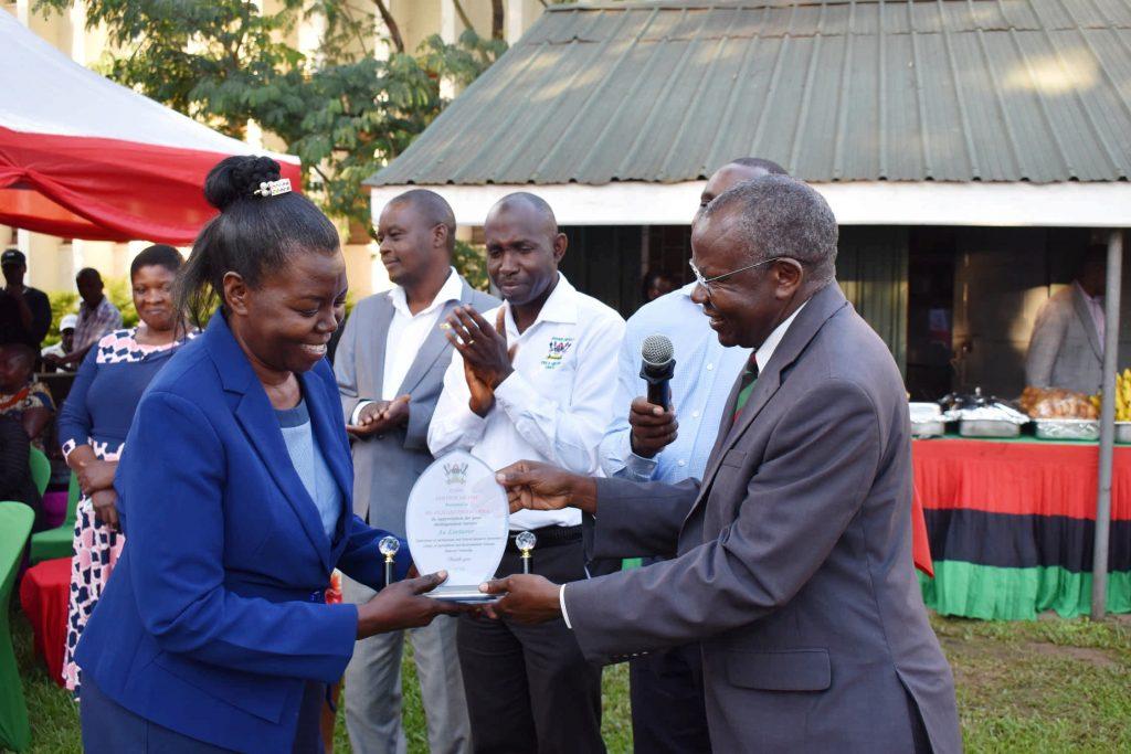 - Ms. Elizabeth Balirwa receivin the plaque from the Principal